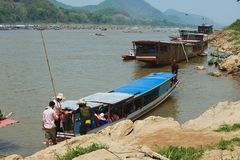 People embark to the traditional long boat to cross Mekong river in dry season in Luang Prabang, Laos. LUANG PRABANG, LAOS - APRIL 12, 2012: Unidentified people royalty free stock photos