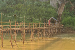 Luang Prabang, Laos - Bamboo bridge across the river with the tourists on them Stock Photography