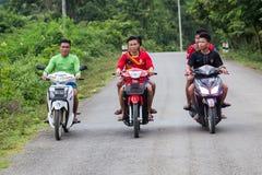 Luang Prabang, Laos - circa agosto de 2015: Muchachos que conducen las motos fuera de Luang Prabang, Laos Imagenes de archivo