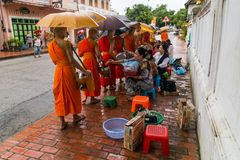 Luang Prabang, Laos - circa August 2015: Traditional Alms giving ceremony of distributing food to buddhist monks on the streets of Royalty Free Stock Photo