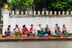 Luang Prabang, Laos - circa August 2015: Traditional Alms giving ceremony of distributing food to buddhist monks on the streets of Royalty Free Stock Image