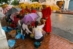 Luang Prabang, Laos - circa August 2015: Traditional Alms giving ceremony of distributing food to buddhist monks on the streets of Royalty Free Stock Photos