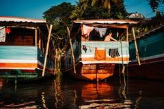 Luang Prabang, Laos, 12/19/2018: Frauen wäscht Kleidung auf einem Hausboot Der Mekong mit Booten neben einander stockfotos