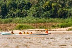 LUANG PRABANG, LAOS - 11 GENNAIO 2017: Monaci in una barca sul fiume di Nam Khan del fiume Copi lo spazio per testo fotografia stock libera da diritti