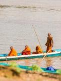 LUANG PRABANG, LAOS - 11 GENNAIO 2017: Monaci in una barca sul fiume di Nam Khan del fiume Copi lo spazio per testo verticale immagine stock libera da diritti
