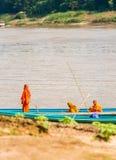 LUANG PRABANG, LAOS - 11 GENNAIO 2017: Monaci in una barca sul fiume di Nam Khan del fiume Copi lo spazio per testo verticale fotografia stock libera da diritti