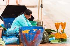LUANG PRABANG, LAOS - JANUARI 11, 2017: Kvinnan säljer offer från sidorna av bananer och blommor Kopiera utrymme för text Arkivfoto