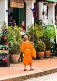 LUANG PRABANG, LAOS - JANUARI 11, 2017: Liten munk på en stadsgata Kopiera utrymme för text vertikalt Arkivfoto