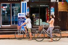 LUANG PRABANG, LAOS - JANUARI 11, 2017: Par av cyklister på stadsgatan Kopiera utrymme för text Royaltyfria Bilder
