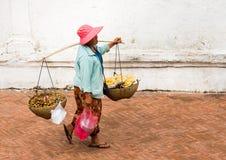 LUANG PRABANG, LAOS - 11 JANVIER 2017 : Femme avec des paniers sur une rue de ville Copiez l'espace pour le texte Images stock