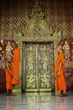 young buddhist monks folding an orange textile in front of a nicely decorated golden plated wooden door royalty free stock photo