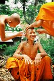 young buddhist monks shaving each others head in preparation for a holy festival event royalty free stock photography