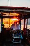 Luang Prabang, Laos, 12 19 18: Kapitän auf Schiff nimmt Touristen auf einer Sonnenuntergangkreuzfahrt beim Mekong Schöne Sonnenun lizenzfreies stockbild
