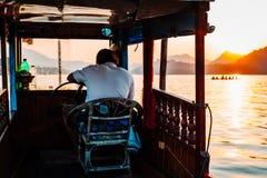 Luang Prabang, Laos, 12 19 18: Kapitän auf Schiff nimmt Touristen auf einer Sonnenuntergangkreuzfahrt beim Mekong Schöner Sonnenu stockbilder