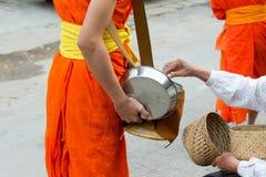 Luang Prabang, Laos - Mars 06 2015: Buddistiska munkar som samlar alm Arkivfoto