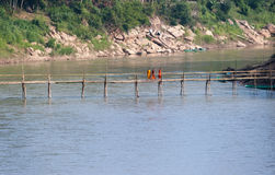 Luang Prabang, Laos. Monks crossing wooden bridge Royalty Free Stock Images