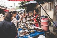 A local Laotian Hill tribe woman cooking food and sells at the daily morning market in Luang Prabang, Laos on the 13th NOVEMBER, 2. LUANG PRABANG, LAOS royalty free stock image