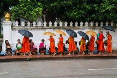 Luang Prabang, Laos - około Sierpień 2015: Tradycyjni datki daje ceremonii zakłócać jedzenie mnisi buddyjscy na ulicach Zdjęcie Stock