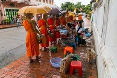Luang Prabang, Laos - około Sierpień 2015: Tradycyjni datki daje ceremonii zakłócać jedzenie mnisi buddyjscy na ulicach Zdjęcie Royalty Free