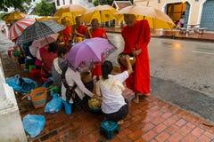 Luang Prabang, Laos - około Sierpień 2015: Tradycyjni datki daje ceremonii zakłócać jedzenie mnisi buddyjscy na ulicach Zdjęcia Royalty Free