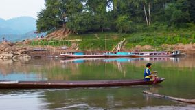 LUANG PRABANG, LAOS: Unidentified man row by traditional wooden boat on calm river near wooden bridge stock video footage