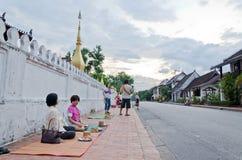 LUANG PRABANG, LAOTIANO - 12 MAGGIO: Turista che aspetta i monaci ogni Fotografia Stock Libera da Diritti