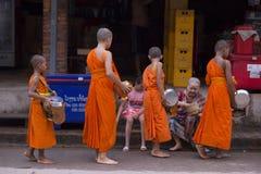 Luang Prabang, le Laos, jeunes moines et les gens dans donner d'aumône photographie stock libre de droits