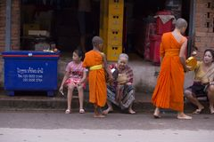 Luang Prabang, le Laos, jeunes moines et les gens dans donner d'aumône image stock