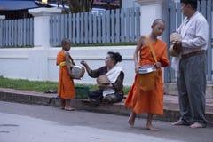 Luang Prabang, le Laos, jeunes moines et les gens dans l'aumône donnant c images stock