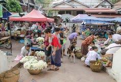 LUANG PRABANG-MAY 2014: På en morgonmarknad i staden en försäljare Arkivbild