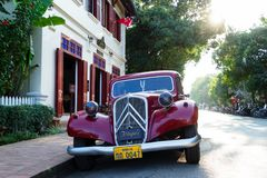 LUANGPRABANG LAOS - JANUARI 16, 2018: Sikten på en klassisk retro röd bil på en gata parkerade nära till restaurangen Arkivbild