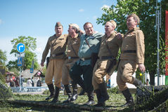 LUBAN, BELARUS - MAY 9, 2015: a group of men in uniform of Soviet soldiers performing a dance Stock Photos