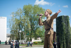 LUBAN, BELARUS - MAY 9, 2015: a man wearing the uniform of a Soviet soldier sings a song on stage Stock Image