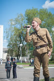 LUBAN, BELARUS - MAY 9, 2015: a man wearing the uniform of a Soviet soldier sings a song on stage Stock Photo