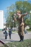 LUBAN, BIELORRUSIA - 9 DE MAYO DE 2015: un hombre que lleva el uniforme de un soldado soviético canta una canción en etapa Fotografía de archivo
