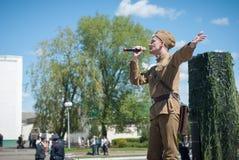 LUBAN, BIELORUSSIA - 9 MAGGIO 2015: un uomo che porta l'uniforme di un soldato sovietico canta una canzone in scena Immagine Stock