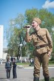 LUBAN, BIELORUSSIA - 9 MAGGIO 2015: un uomo che porta l'uniforme di un soldato sovietico canta una canzone in scena Fotografia Stock