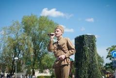 LUBAN, WEISSRUSSLAND - 9. MAI 2015: ein Mann, der die Uniform eines sowjetischen Soldaten trägt, singt ein Lied auf Stadium Stockbilder
