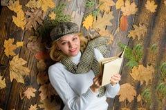 Lubi detektywistycznego gatunku Dziewczyny blondynka kłaść drewnianego tło z liśćmi Kobiety dama w w kratkę kapeluszu i szaliku c zdjęcia stock