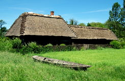 Lublin, Poland: Farmstead with Thatched Roof. A wooden boat beached on a grassy field in back of a fine 19th century farmstead with house and barn, both with Royalty Free Stock Images