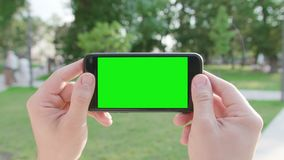 Hands Holding a Phone with a Green Screen