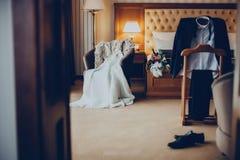 Ślubna suknia, kostium i bukiet w pokoju hotelowym, Zdjęcia Stock