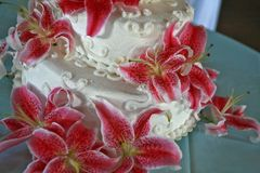 Ślubny tort z wiele czerwonymi lelujami Obraz Royalty Free