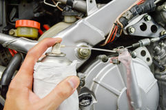 Lubricating the motorbike. Close up of hand pushing spray in motorcycle motor Royalty Free Stock Image