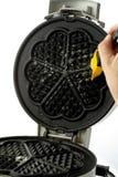 Lubrificando o ferro de waffle com escova, close-up Imagens de Stock Royalty Free