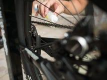 Lubrificando uma corrente e uma engrenagem da bicicleta com garrafa de óleo Fotos de Stock Royalty Free