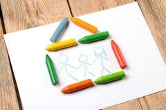 Lubrifichi i pastelli pastelli che si trovano su una carta con la famiglia dipinta Fotografie Stock Libere da Diritti
