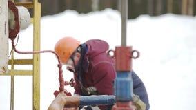Lubrifichi il lavoratore e la pompa Jack, lavoratore nell'azione al pozzo di petrolio della presa della pompa stock footage