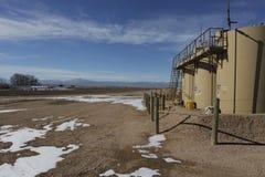 Lubrifichi l'impianto di perforazione di Fracking vicino ad una casa nel terreno coltivabile di Colorado. Immagini Stock Libere da Diritti