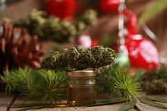Lubrifichi la cannabis in una bottiglia e la canapa su un fondo di natale fotografia stock libera da diritti